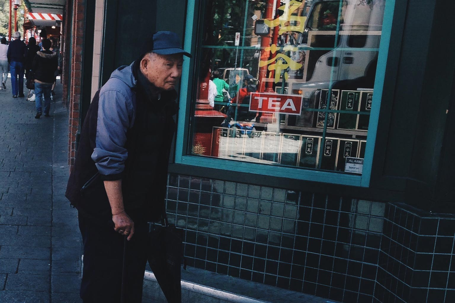 elderly man walking through Chinatown