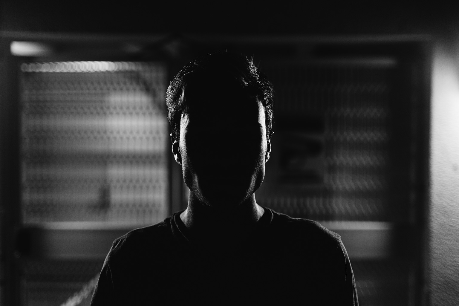 man in darkness with face hidden