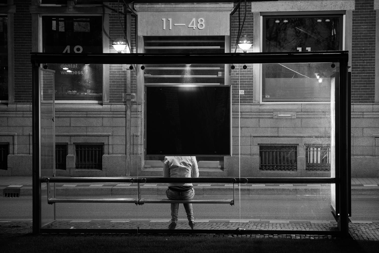 woman sitting alone at bus stop